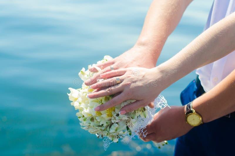 Mãos do ` s dos noivos do close-up com alianças de casamento e ramalhete Amor e união Acessórios e decoração do casamento no back imagem de stock royalty free