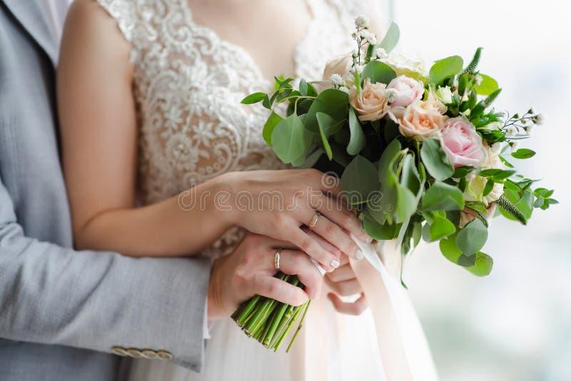Mãos do ` s dos noivos com alianças de casamento imagens de stock royalty free