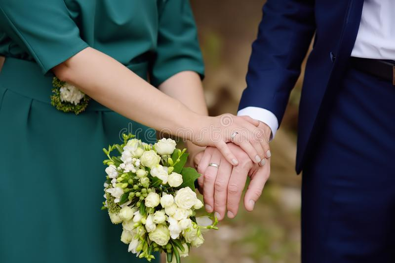 Mãos do ` s dos noivos com alianças de casamento fotos de stock royalty free