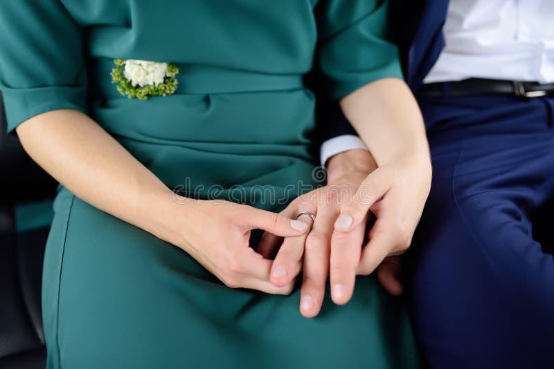 Mãos do ` s dos noivos com alianças de casamento imagem de stock royalty free