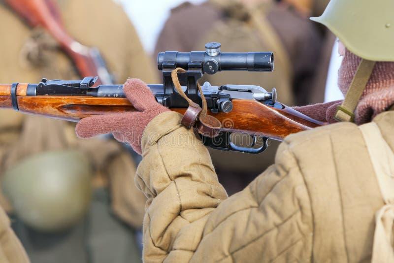 Mãos do soldado ou do atirador furtivo que guardam a arma imagem de stock royalty free