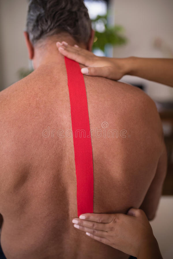 Mãos do terapeuta fêmea que aplicam a fita terapêutica elástica na parte traseira masculina superior descamisado do paciente imagem de stock royalty free