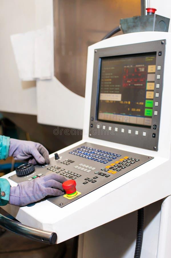 Mãos do trabalhador no painel de controle de uma máquina programável do cnc imagem de stock royalty free