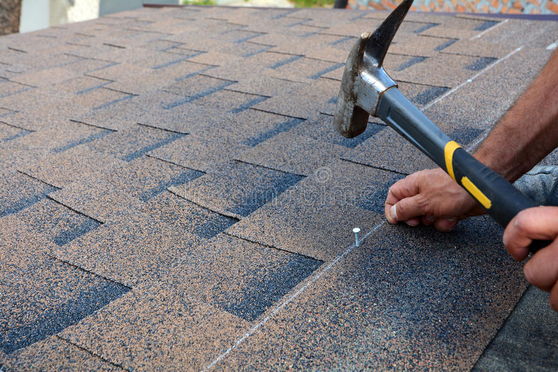 Mãos do trabalhador que instalam telhas do telhado do betume Martelo do trabalhador nos pregos no telhado O Roofer está marteland fotos de stock