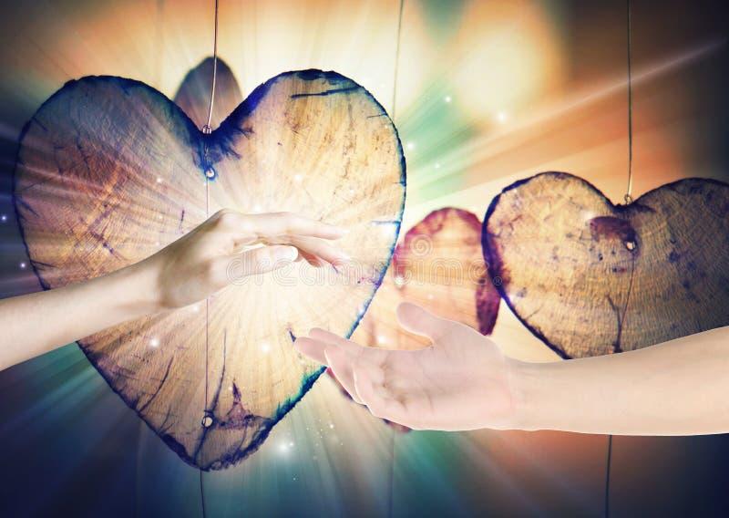 Mãos dos amantes que alcançam para fora na luz divina fotografia de stock