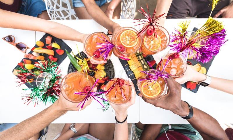Mãos dos amigos que brindam bebidas do verão na barra do cocktail no happy hour fotografia de stock