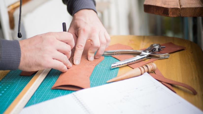 Mãos dos curtidores no trabalho com couro Perfurador do revólver e uma capa impermeável Foco selecionado, fim acima fotografia de stock royalty free