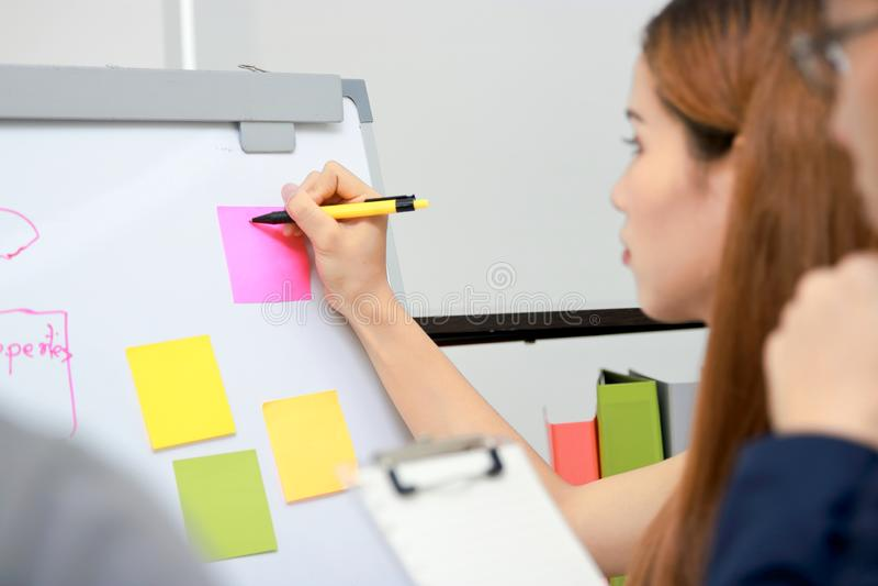 Mãos dos executivos asiáticos que explicam estratégias na carta de aleta na sala de conferências fotos de stock royalty free