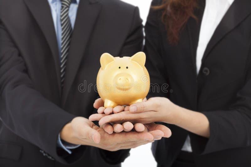 Mãos dos executivos que guardam um mealheiro Pena, eyeglasses e gráficos fotos de stock royalty free