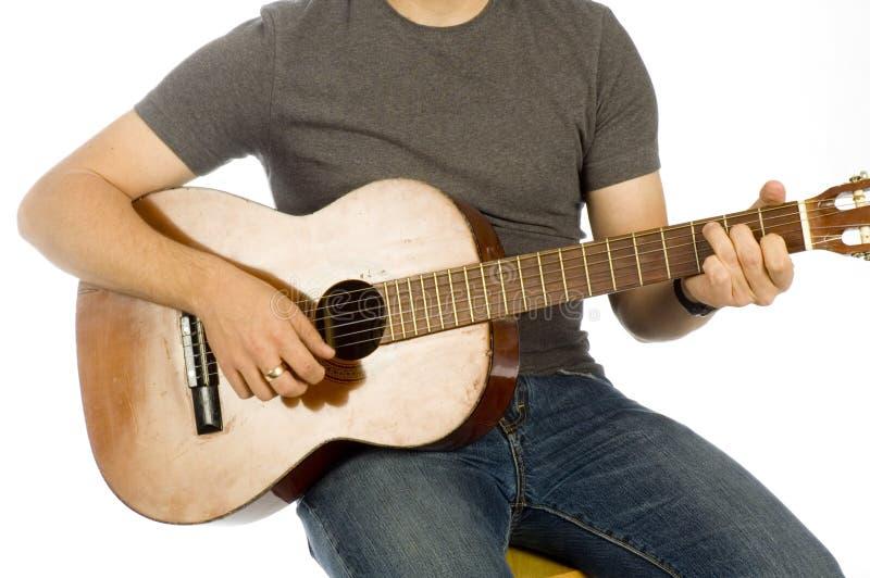 Mãos dos guitarristas que jogam o instrumento imagem de stock royalty free
