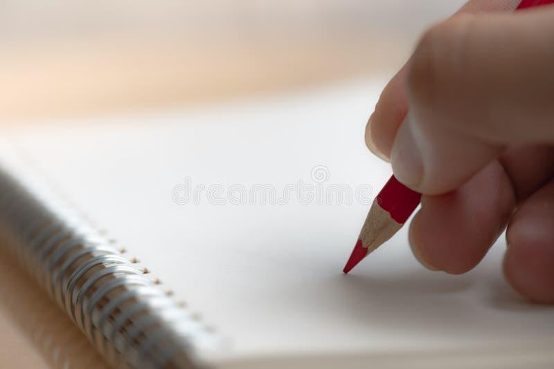 M?os dos homens com escrita do l?pis no caderno imagens de stock royalty free