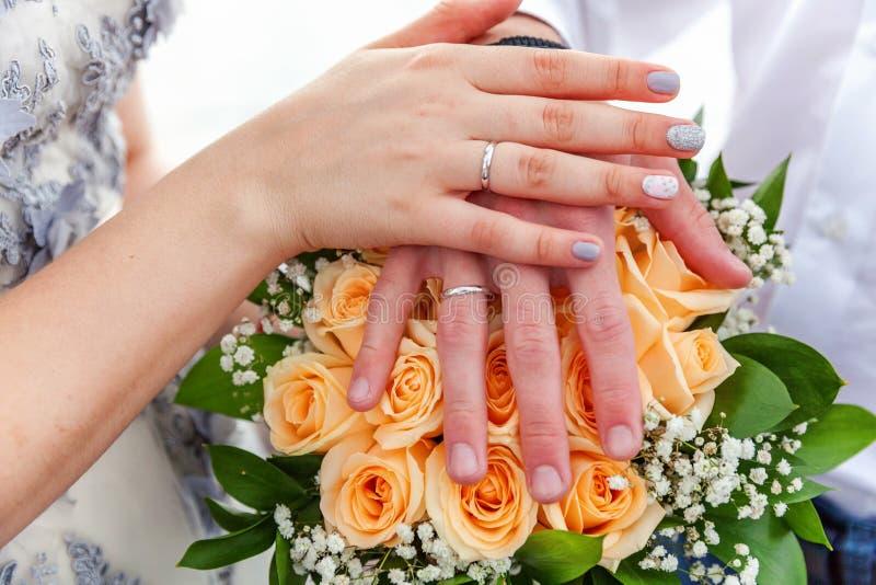Mãos dos noivos com alianças de casamento contra o fundo do ramalhete nupcial das flores imagem de stock