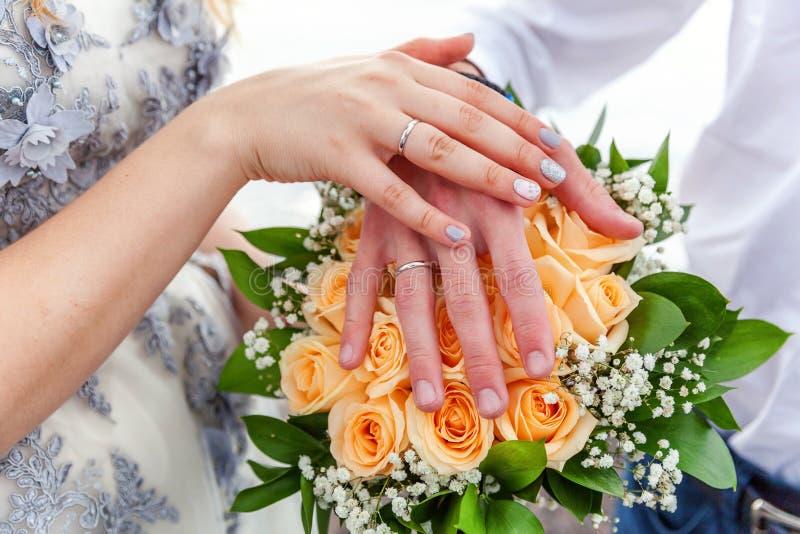 Mãos dos noivos com alianças de casamento contra o fundo do ramalhete nupcial das flores imagem de stock royalty free