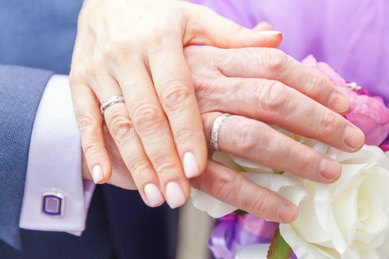 Mãos dos noivos com alianças de casamento contra o fundo do ramalhete nupcial das flores fotos de stock