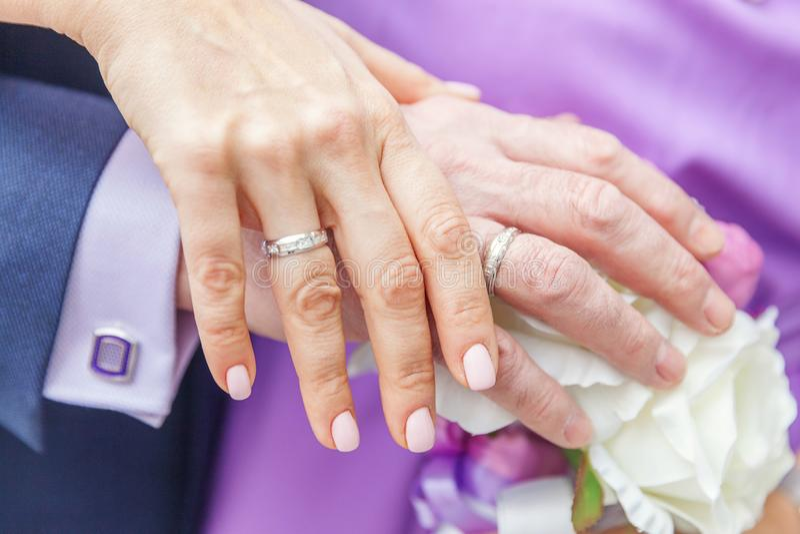 Mãos dos noivos com alianças de casamento contra o fundo do ramalhete nupcial das flores fotos de stock royalty free
