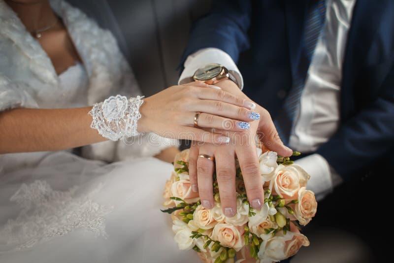 Mãos dos noivos com anéis no ramalhete do casamento fotografia de stock royalty free