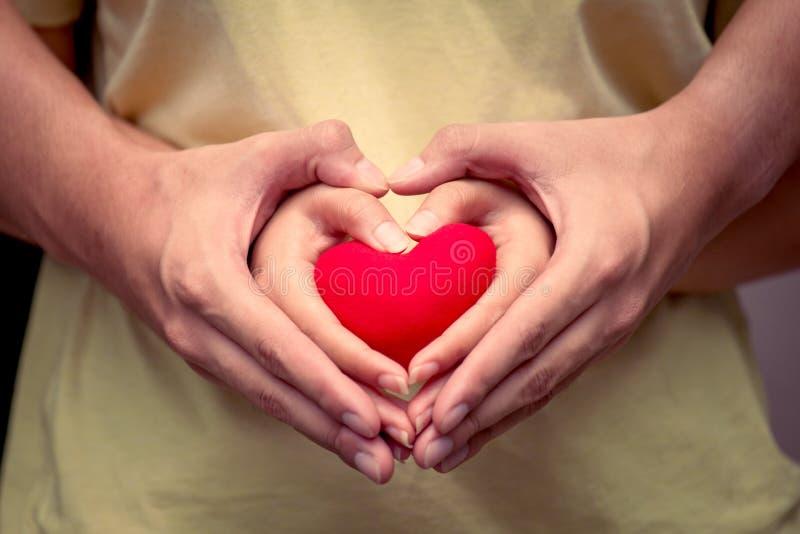 Mãos dos pares do amor com coração vermelho imagens de stock royalty free