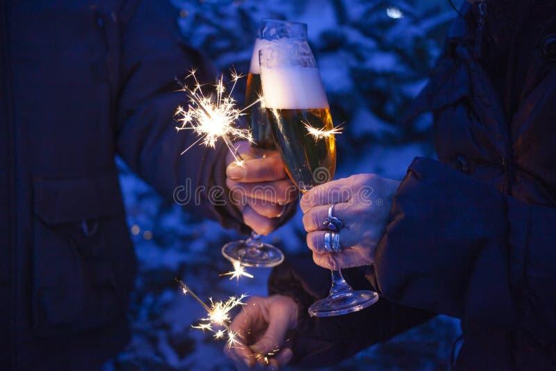 mãos dos pares idosos que mantêm os sparkles e os vidros do champanhe que comemoram o ano novo fotos de stock
