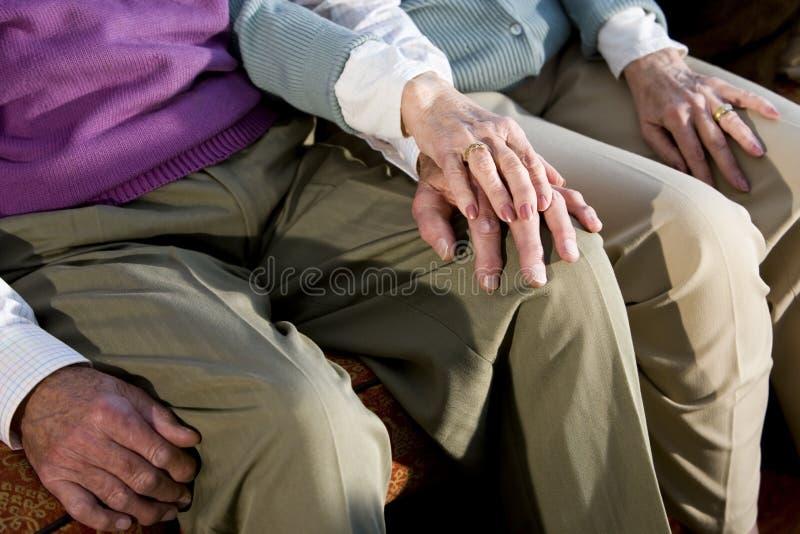 Mãos dos pares idosos que tocam no joelho foto de stock royalty free
