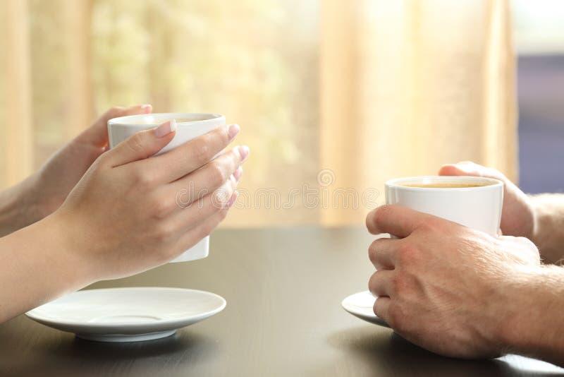 Mãos dos pares ou dos amigos que guardam copos de café imagens de stock