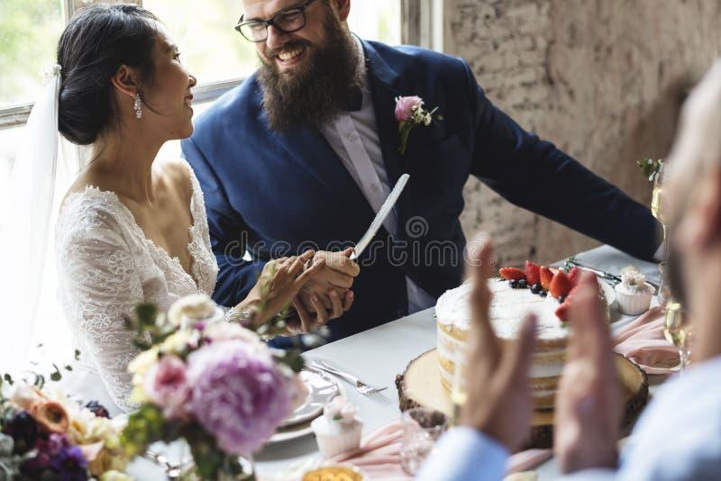 Mãos dos pares que guardam a faca do bolo de casamento imagens de stock royalty free