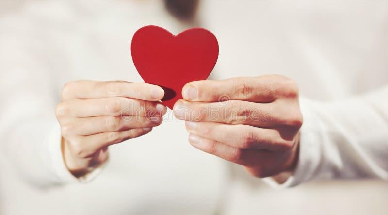 Mãos dos pares que guardam o símbolo do amor da forma do coração fotografia de stock royalty free
