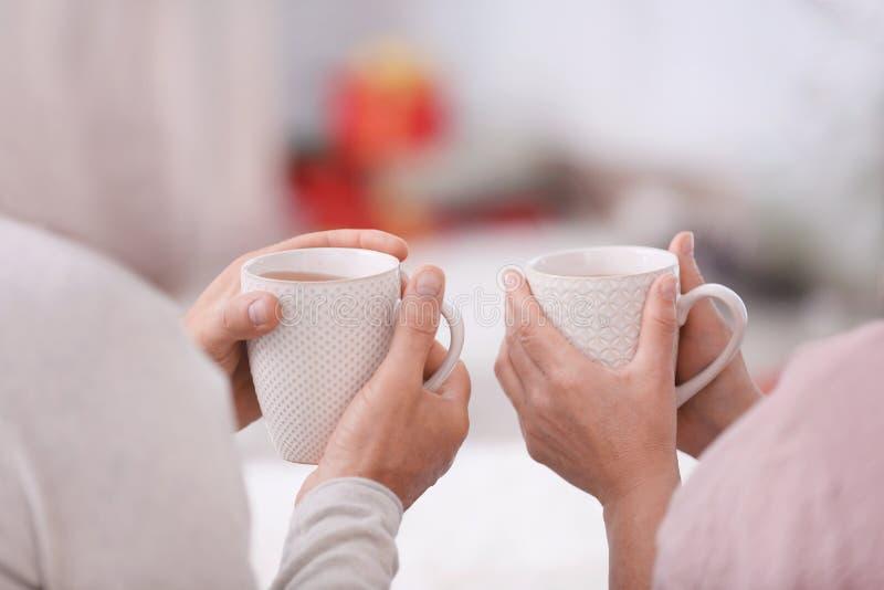 Mãos dos pares superiores felizes que bebem o chá quente em casa fotos de stock