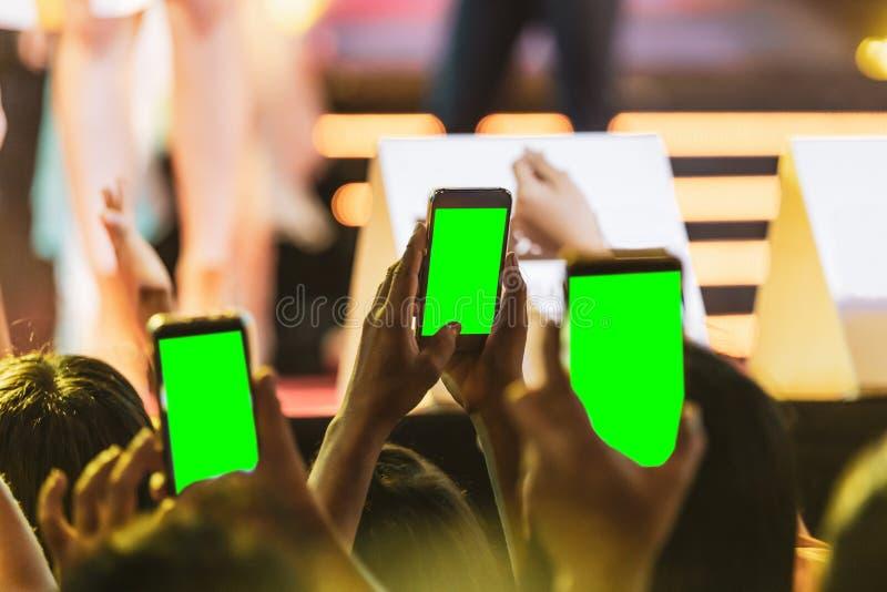 Mãos dos povos da multidão da audiência que tomam a foto com o telefone esperto móvel com a tela verde no concerto do partido fotografia de stock royalty free