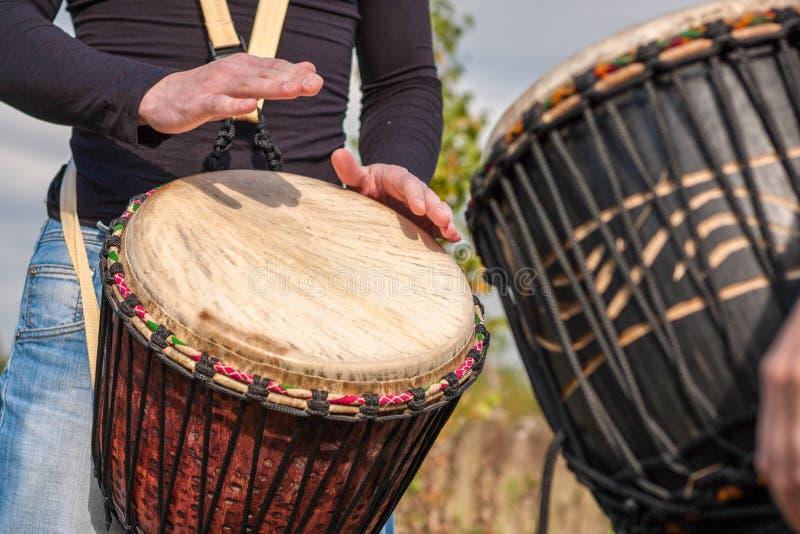 Mãos dos povos que jogam a música em cilindros do djembe fotos de stock