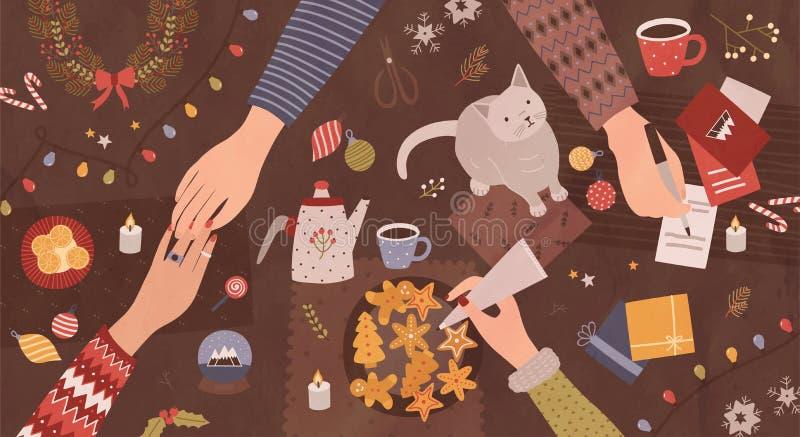 Mãos dos povos que sentam-se em torno da tabela e que preparam-se para o Natal - fazendo decorações festivas, escrevendo em cartõ ilustração stock