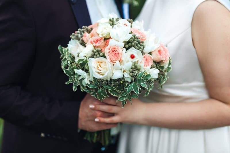 Mãos dos recém-casados com um ramalhete do close-up da noiva conceito da união imagens de stock royalty free