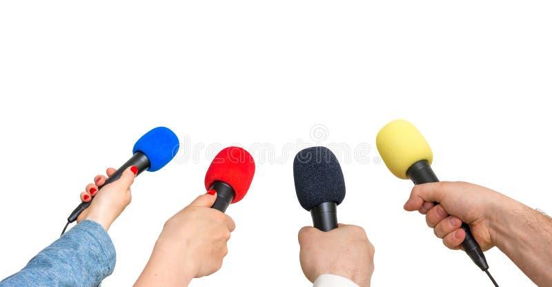 Mãos dos repórteres com muitos microfones isolados no branco fotos de stock royalty free