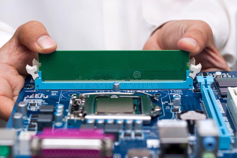 Mãos dos técnicos que instalam a memória do usuário fotos de stock royalty free