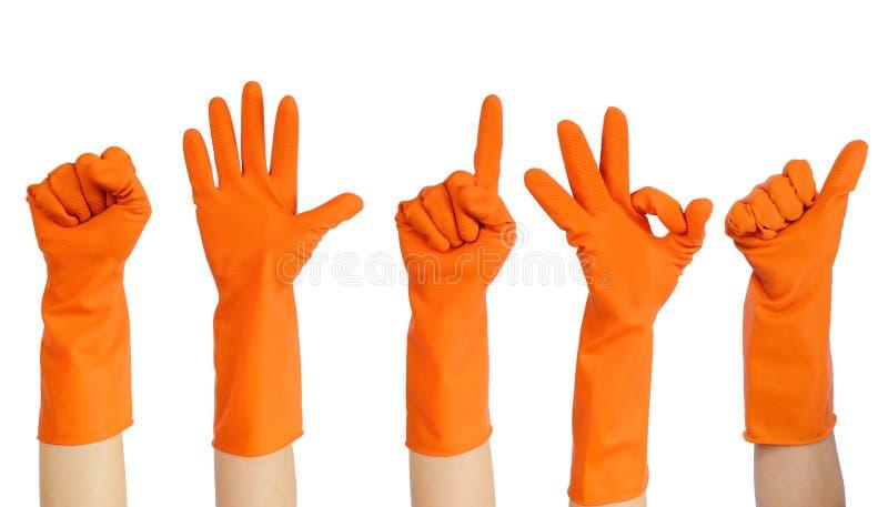 Mãos dos voluntários nas luvas de borracha amarelas que põem acima do isolado sobre o conceito voluntário do fundo branco imagem de stock
