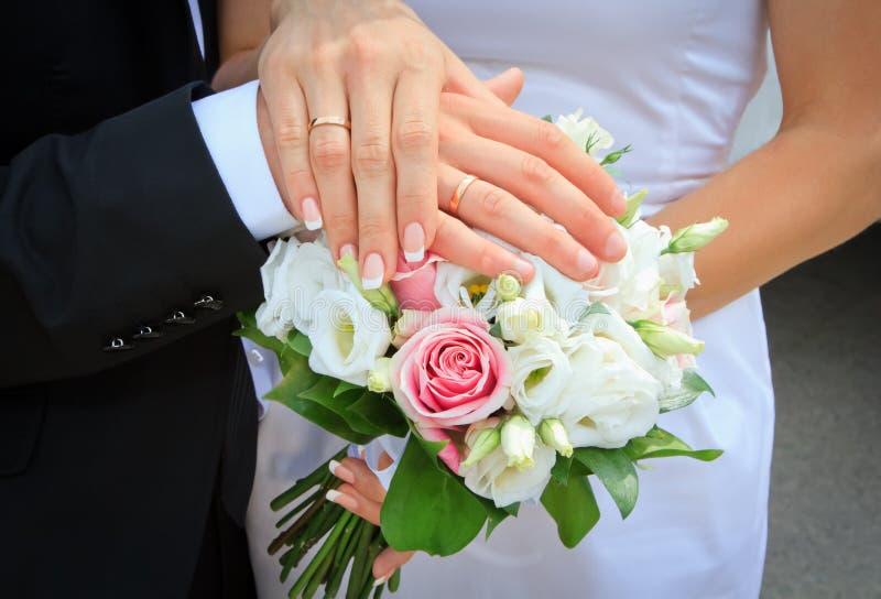 Mãos e anéis no ramalhete do casamento imagem de stock royalty free