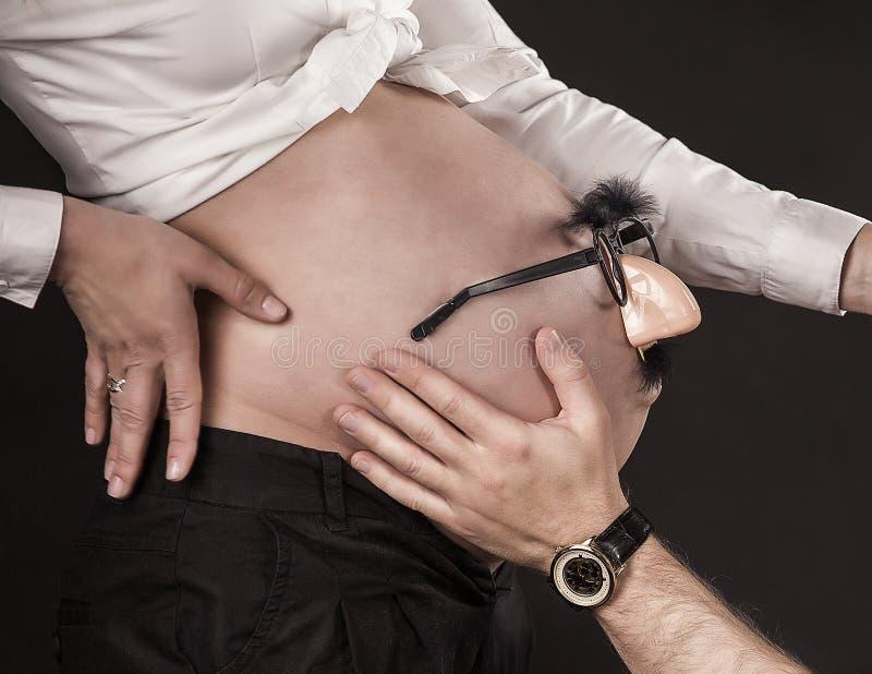 Mãos e barriga - barriga da mulher gravida que guarda as mãos da mãe, do pai e da criança imagem de stock