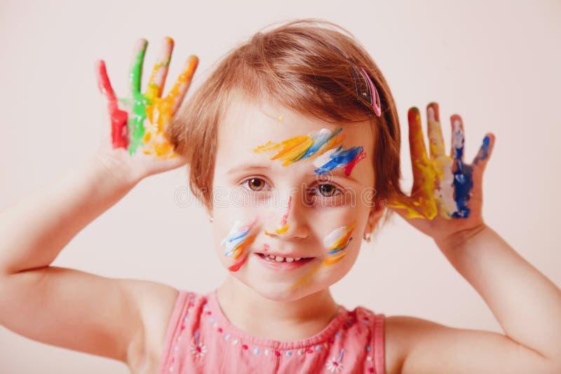 Mãos e cara da menina bonito pintadas em pinturas coloridas Composi??o do ` s das crian?as foto de stock