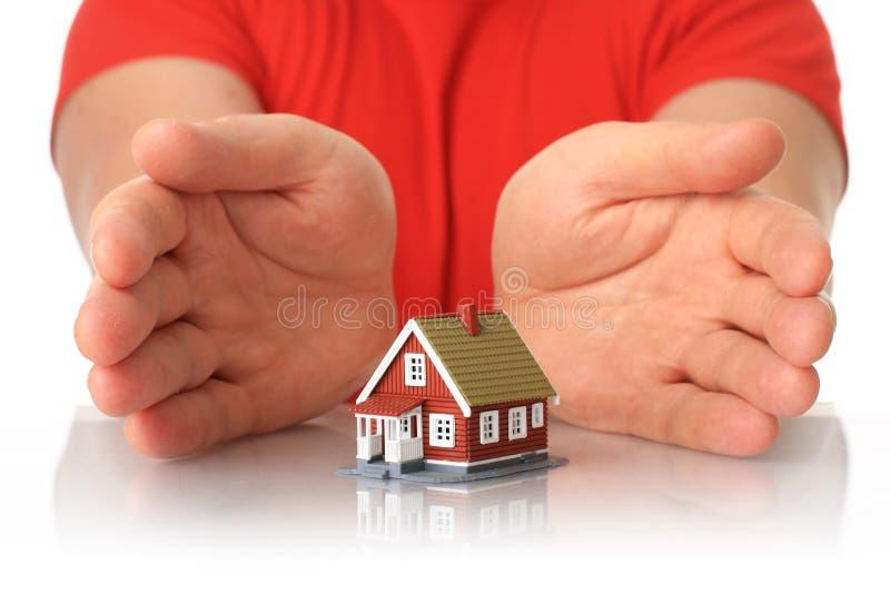 Mãos e casa pequena. imagem de stock
