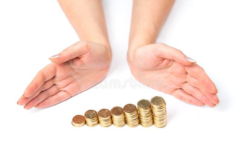 Mãos e moedas no branco imagens de stock