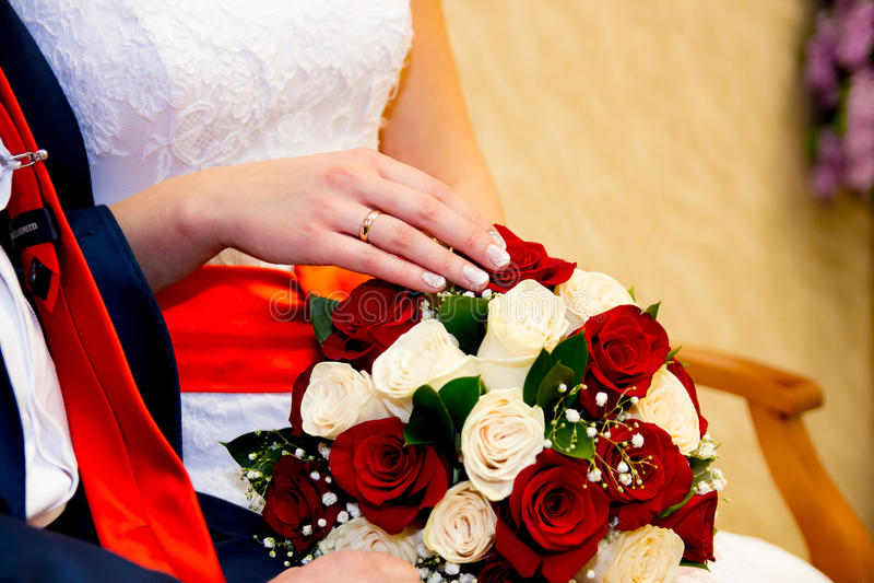 Mãos e noivo da noiva dos anéis no fundo de um ramalhete do casamento foto de stock