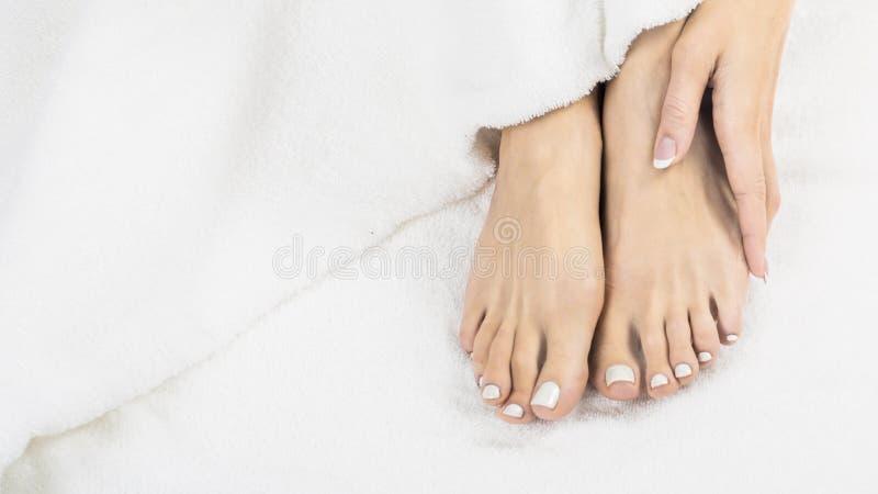 Mãos e pés bonitos de mulheres saudáveis na cama imagem de stock