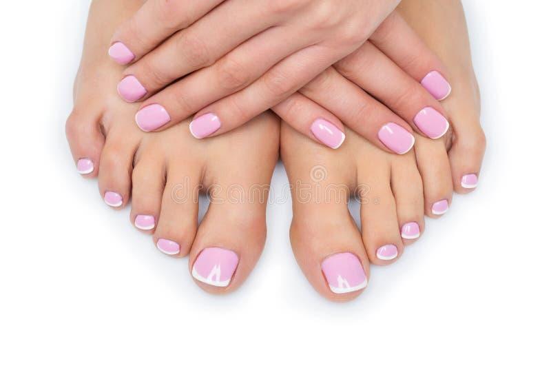 Mãos e pés da mulher com tratamento de mãos francês imagem de stock