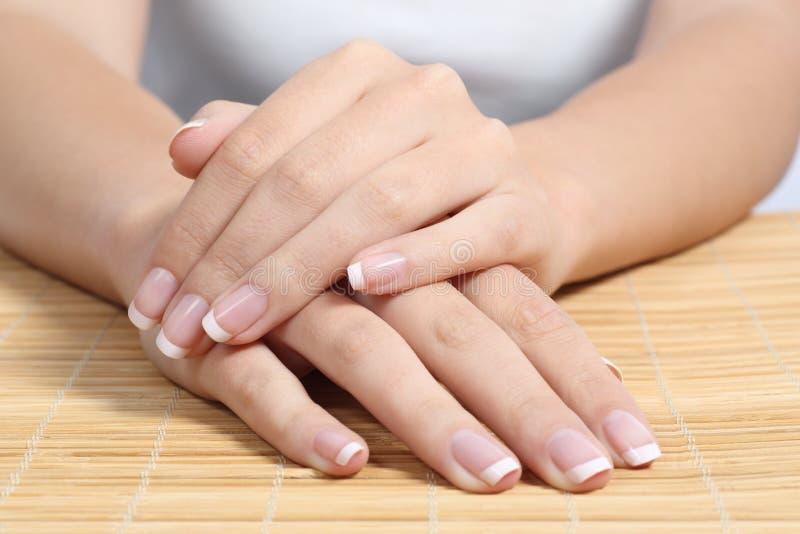 Mãos e pregos bonitos da mulher com tratamento de mãos francês perfeito fotos de stock