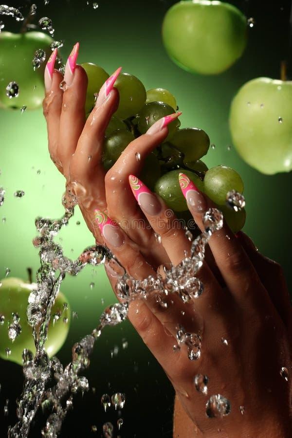 Mãos e pregos bonitos no fundo verde imagens de stock