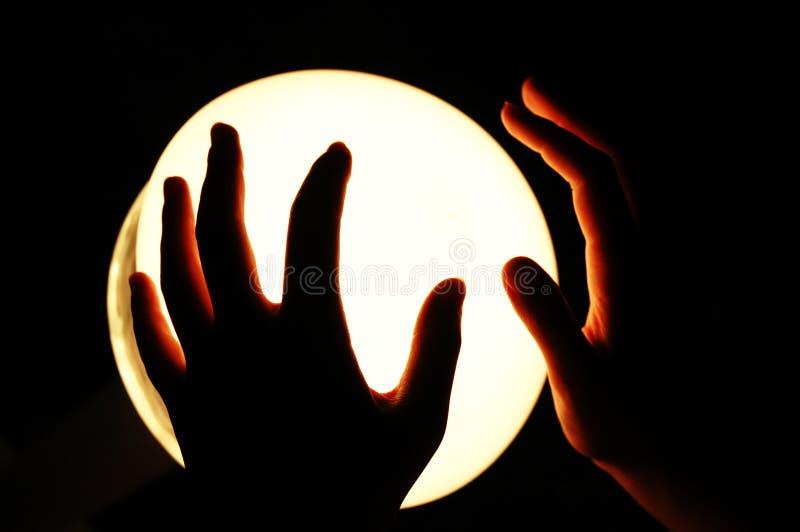 Mãos em um globo de incandescência fotos de stock