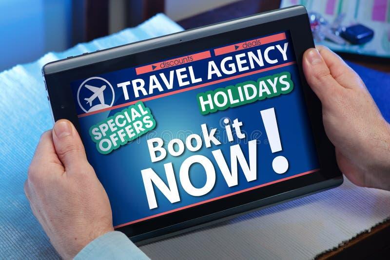 Mãos em uma tabuleta que olha uma agência de viagens em linha da página imagem de stock royalty free