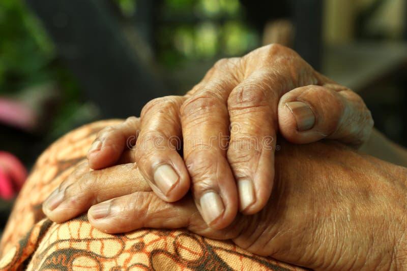 Mãos enrugadas dobradas no close up do regaço fotos de stock royalty free