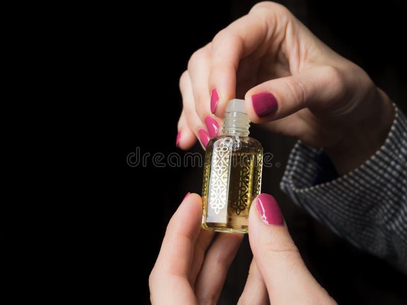 Mãos europeias de uma mulher com óleo árabe do perfume imagens de stock