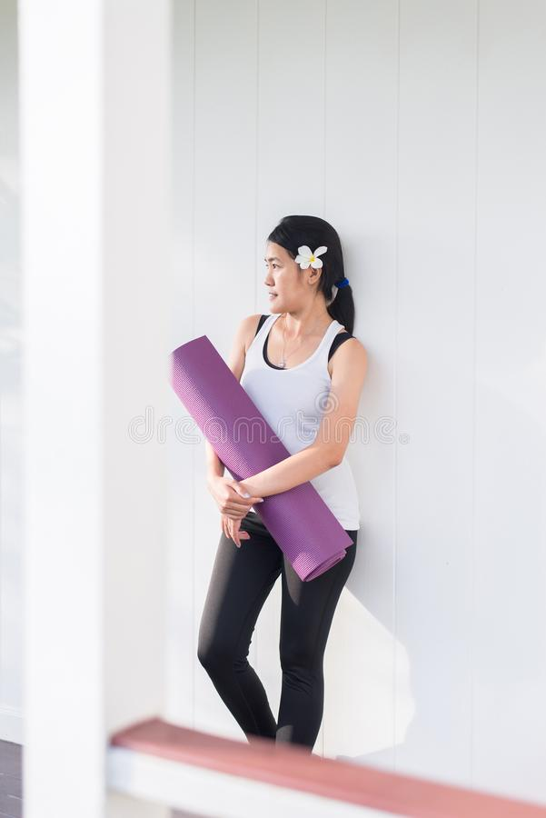 M?os f?meas asi?ticas desportivas que guardam a esteira da ioga ap?s um exerc?cio, um equipamento do exerc?cio, uma aptid?o saud? fotos de stock
