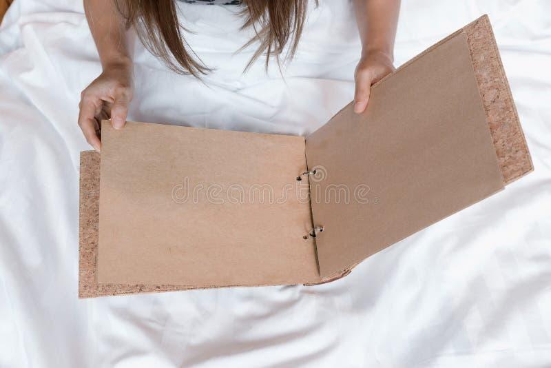 Mãos fêmeas asiáticas que giram páginas marrons vazias na cama branca imagens de stock royalty free